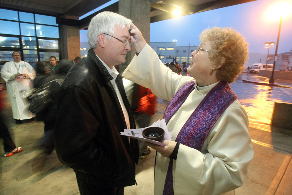 Rev. Kathleen Kingslight of St. Paul's Episcopal Church of Bremerton, Wash.  offers the application of ashes to commuter David Carnahan at the Bremerton Transportation Center on Wednesday, Feb. 22, 2012.   (AP Photo/Kitsap Sun, Larry Steagall)