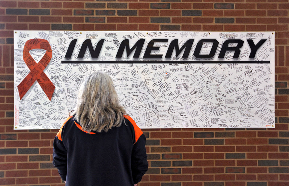 Photo - Betty Tanner read messages left on the memory banner during the memorial service for Oklahoma State head basketball coach Kurt Budke and assistant coach Miranda Serna at Gallagher-Iba Arena on Monday, Nov. 21, 2011 in Stillwater, Okla. The two were killed in a plane crash along with former state senator Olin Branstetter and his wife Paula while on a recruiting trip in central Arkansas last Thursday. Photo by Chris Landsberger, The Oklahoman