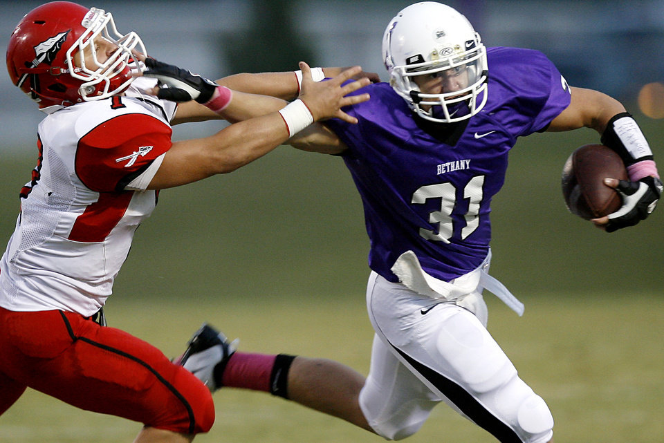 Photo - Bethany's Brett Gilstrap gets past Washington's Zeke Zimmer during their high school football game in Bethany, Okla., on Friday, September 16, 2011. Photo by John Clanton, The Oklahoman