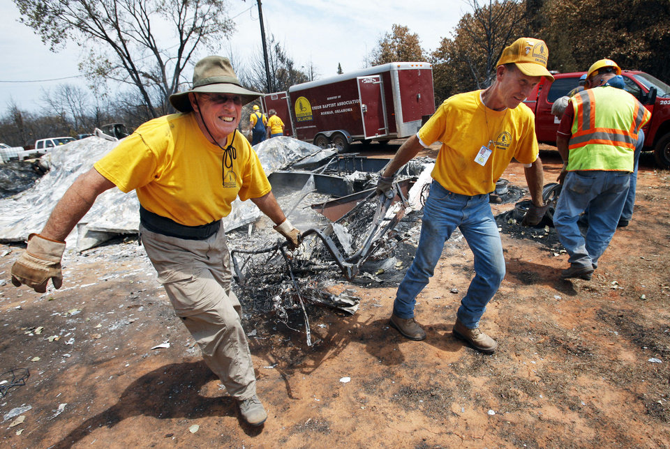 Jim Cook, left, of Choctaw, and Paul Hickerson, of Mountain Park, remove debris Tuesday as volunteers with the Baptist General  Convention of Oklahoma�s disaster relief team clean up a property in Norman after last week�s wildfires. Photo by Steve Sisney, The Oklahoman