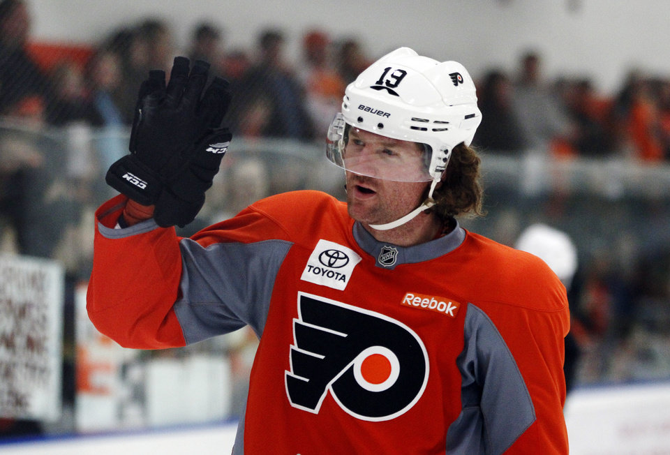 Photo - Philadelphia Flyers' Scott Hartnell waves to fans at the start of the first training camp practice session at the team's training facility Sunday, Jan. 13, 2013, in Voorhees, NJ. The Flyers, and other NHL teams, returned after a 113-day lockout ended with an settlement on a new collective bargaining agreement. (AP Photo/Tom Mihalek)