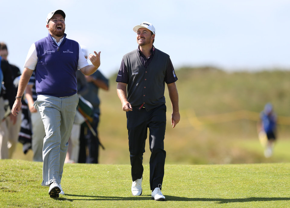Photo - Graeme McDowell of Northern Ireland and Shane Lowry of Ireland, left, talk as they walk along the 14th fairway during a practice round ahead of the British Open Golf championship at the Royal Liverpool golf club, Hoylake, England, Tuesday July 15, 2014. The British Open starts on Thursday July 17. (AP Photo/Scott Heppell)