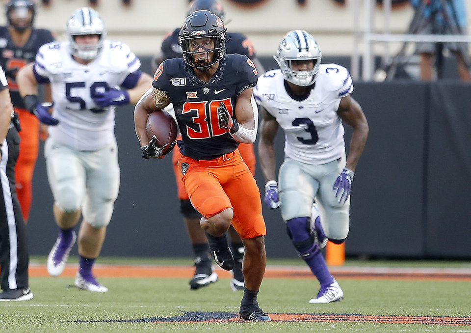 Photo - Oklahoma State's Chuba Hubbard (30) rushes for a big gain as Kansas State's Drew Wiley (59) and Elijah Sullivan (3) chase him in the first quarter during the college football game between the Oklahoma State Cowboys and the Kansas State Wildcats at Boone Pickens Stadium in Stillwater, Okla., Friday, Sept. 27, 2019. [Sarah Phipps/The Oklahoman]