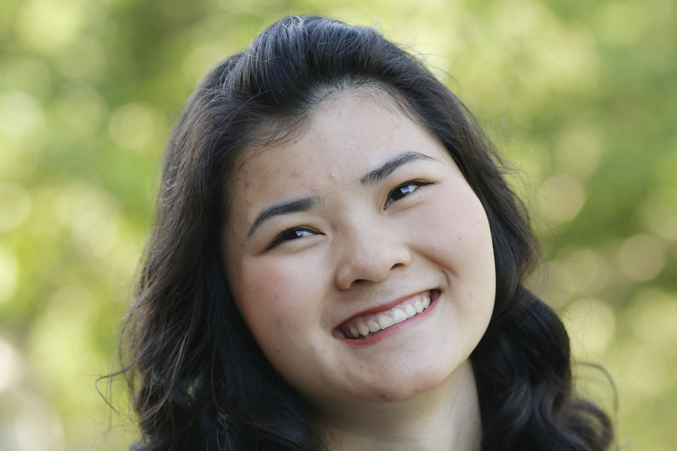 Photo -  Abbey Grace White, 17, who was adopted from a Chinese orphanage, is planning to return to China to help orphans during a summer trip. Photo by Doug Hoke, The Oklahoman   DOUG HOKE -