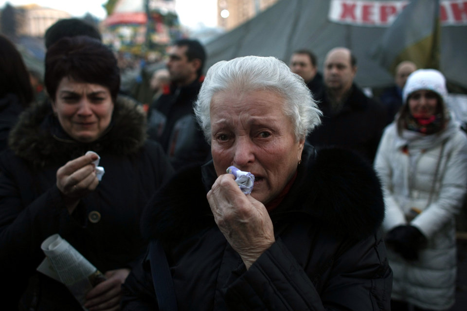 Photo - A woman cries during a funeral procession for anti-government protesters killed in clashes with the police at Independence Square in Kiev, Ukraine, Friday, Feb. 21, 2014. In a day that could significantly shift Ukraine's political destiny, opposition leaders signed a deal Friday with the country's beleaguered president that calls for early elections, a new constitution and a new unity government. (AP Photo/ Marko Drobnjakovic)