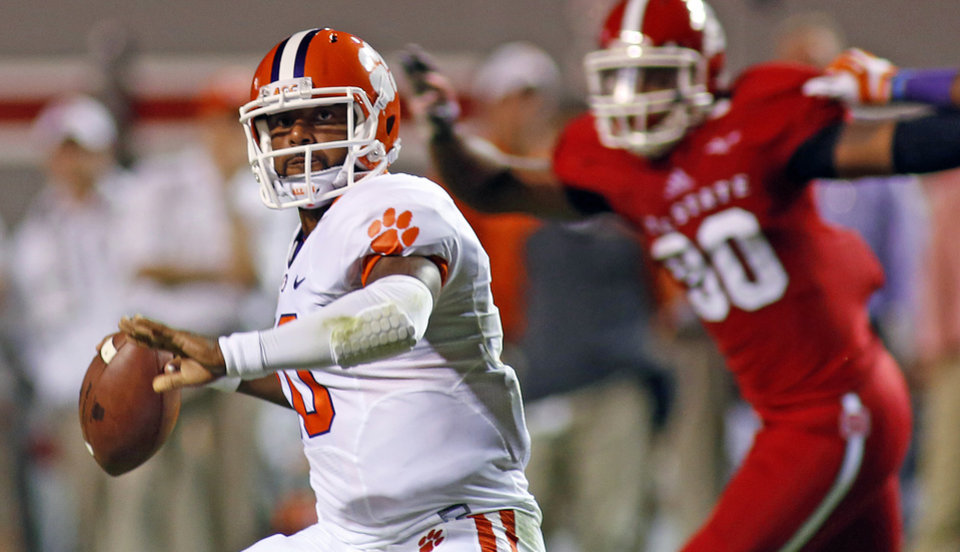 Clemson's Tajh Boyd, left, looks to pass the ball during the first half of an NCAA college football game against North Carolina State in Raleigh, N.C., Thursday, Sept. 19, 2013. (AP Photo/Karl B DeBlaker)