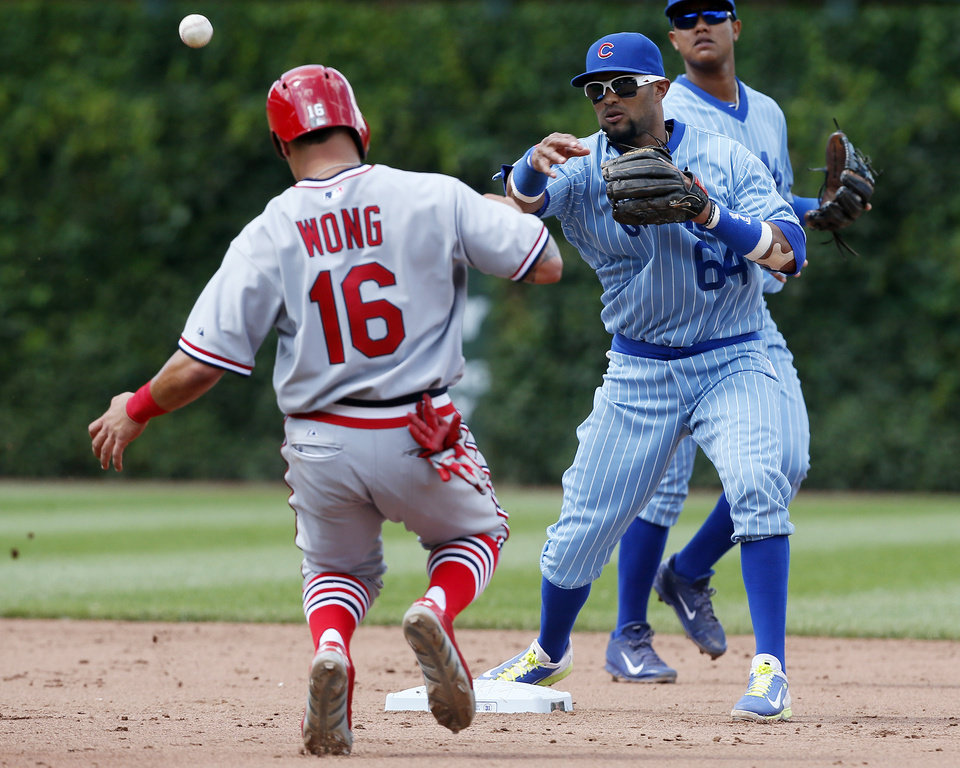 Photo - Chicago Cubs second baseman Emilio Bonifacio forces out the St. Louis Cardinals' Kolten Wong on a double play hit by Matt Holliday during the sixth inning of a baseball game on Sunday, July 27, 2014, in Chicago. (AP Photo/Andrew A. Nelles)