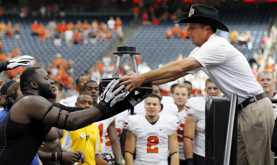 OSU head coach Mike Gundy hands the trophy to Calvin Barnett after the AdvoCare Texas Kickoff college football game between the Oklahoma State University Cowboys (OSU) and the Mississippi State University Bulldogs (MSU) at Reliant Stadium in Houston, Saturday, Aug. 31, 2013. OSU won, 21-3. Photo by Nate Billings, The Oklahoman