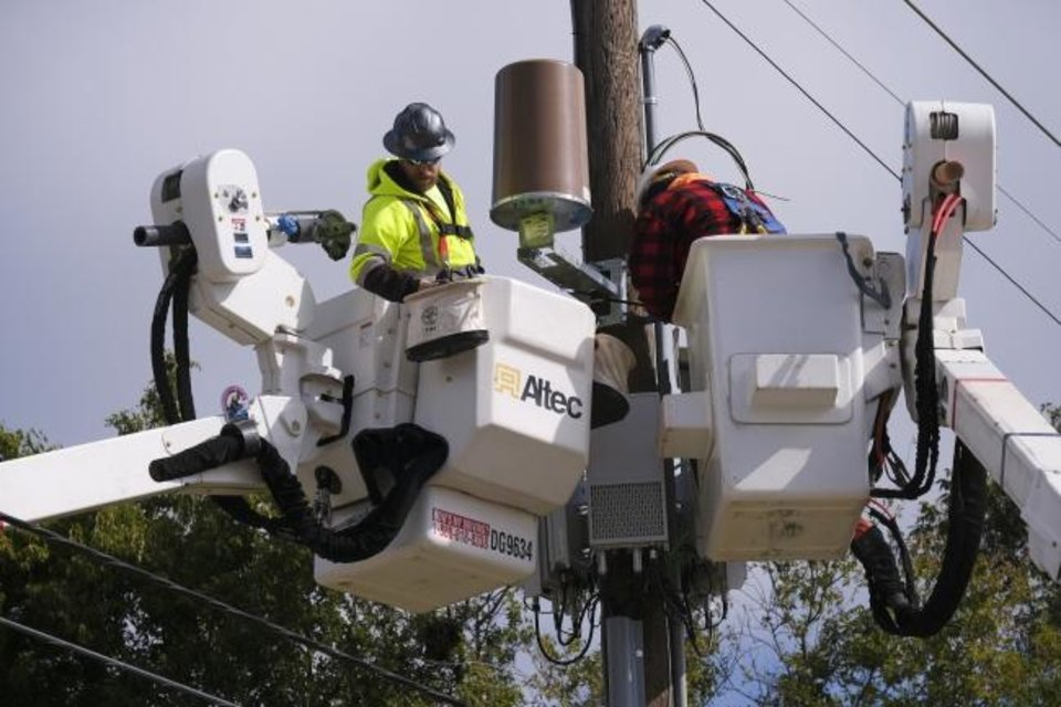 Photo -  Crews work late last week to restore power on Lincoln Boulevard in Oklahoma City. OG&E estimates it should have power fully restored in the metro by the end of the weekend. [Doug Hoke/The Oklahoman]