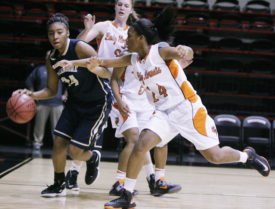 Photo - Booker T. Washington Hornets No.14 Tori Cooks guards Southmoore Lady Sabercats No.24 Kyeria Hannah during the class 6A state tournament girls quarterfinal basketball game in Skiatook, Okla., taken on March 7,2013. JAMES GIBBARD/Tulsa World