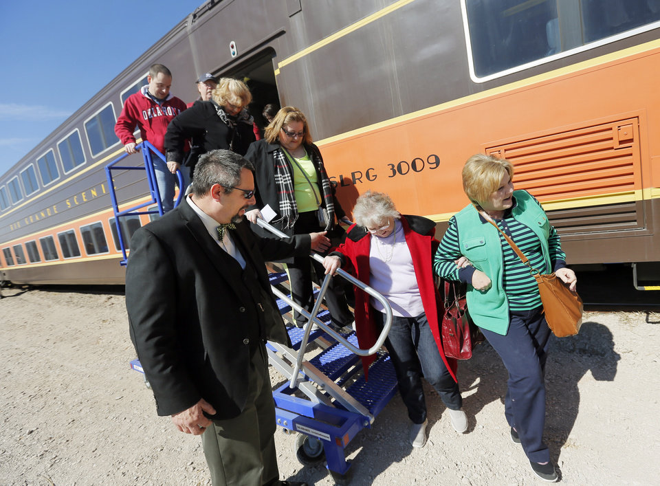Photo - Jody Moore of Chicago with the Pullman Sleeping Car Co. helps passengers leave the train after a demonstration ride of the Eastern Flyer passenger train from Sapulpa to the Oklahoma City metro area, Sunday, Feb. 23, 2014. Photo by Nate Billings, The Oklahoman