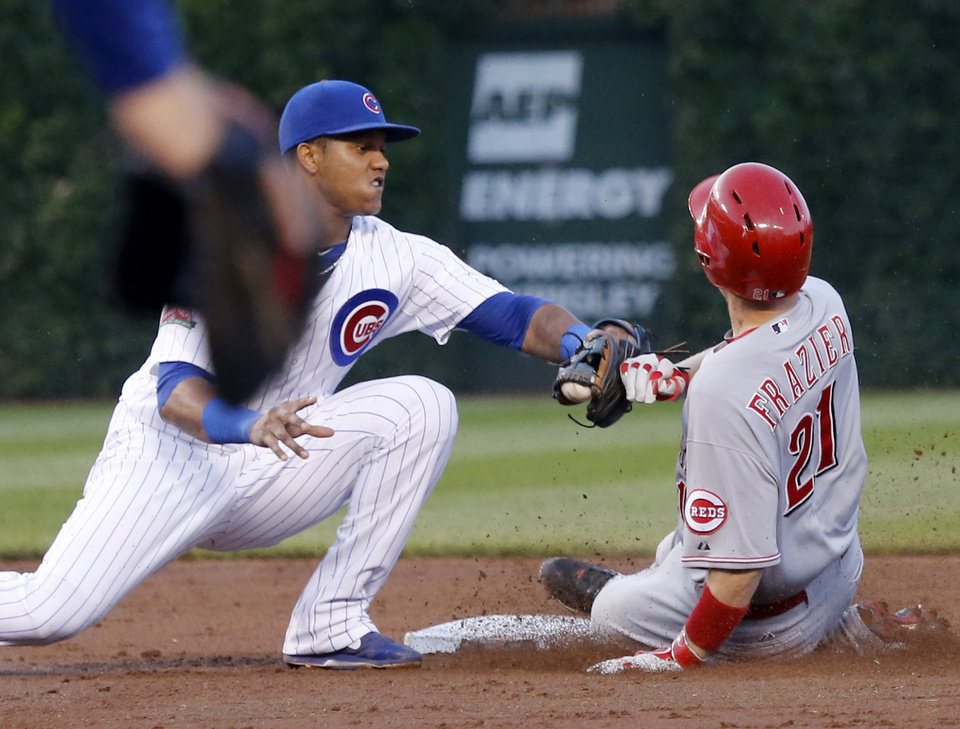 Photo - Chicago Cubs shortstop Starlin Castro, left, tags out Cincinnati Reds' Todd Frazier at second, on a throw from right fielder Ryan Sweeney, after Fraizer tried to extend his hit to a double during the third inning of a baseball game Monday, June 23, 2014, in Chicago. (AP Photo/Charles Rex Arbogast)