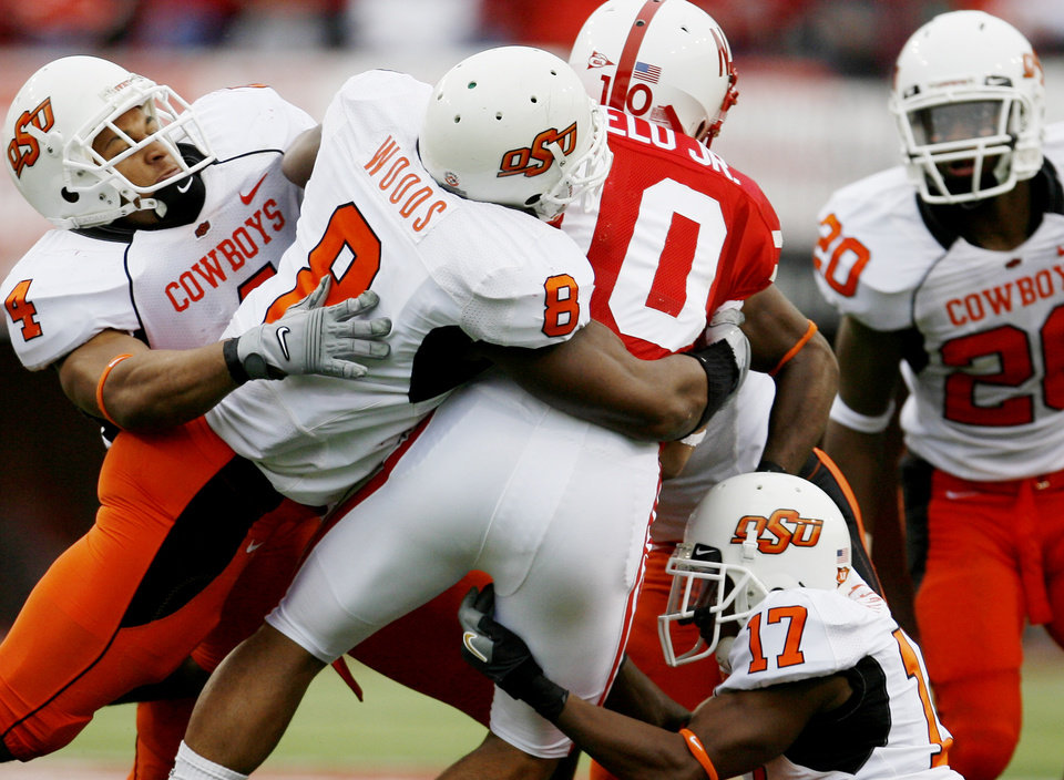 Photo - Patrick Lavine, left, Donovon Woods, and Jacob Lacey tackle Roy Helu of Nebraska during  the college football game between Oklahoma State University (OSU) and the University of Nebraska at Memorial Stadium in Lincoln, Neb., on Saturday, Oct. 13, 2007. By Bryan Terry, The Oklahoman