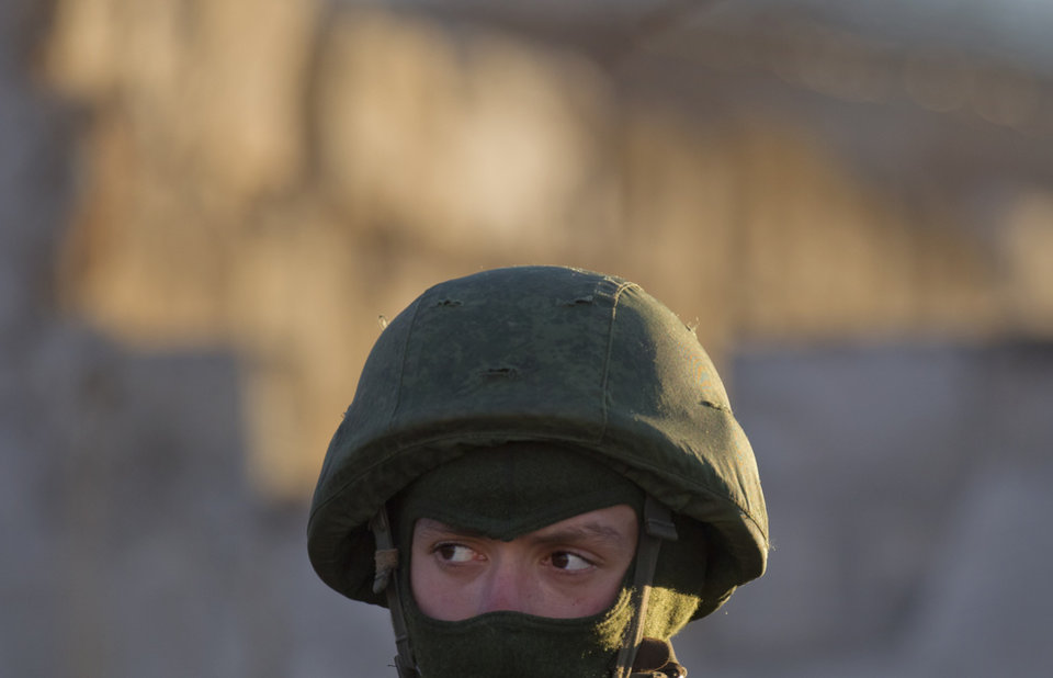 Photo - A pro-Russian soldier stands close to the main gate of an Ukrainian military base in Perevalne, Ukraine, Saturday, March 15, 2014. Tensions are high in the Black Sea peninsula of Crimea, where a referendum is to be held Sunday on whether to split off from Ukraine and seek annexation by Russia. (AP Photo/Vadim Ghirda)