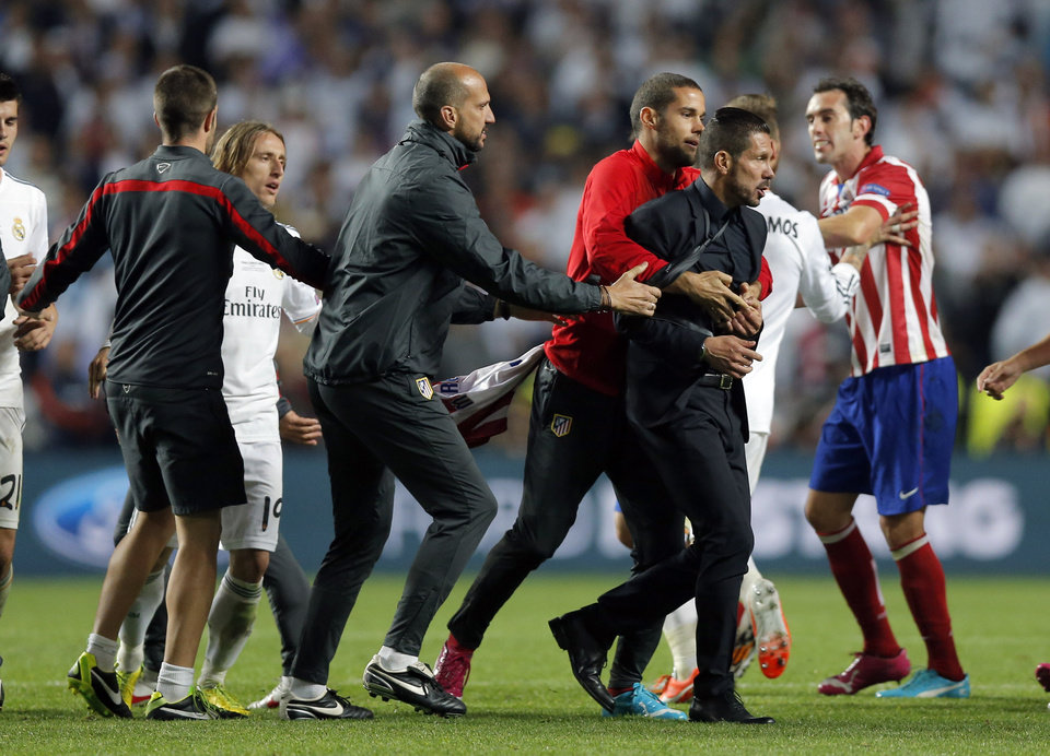 Photo - Atletico's coach Diego Simeone, centre right,  is held back by his staff, during the Champions League final soccer match between Atletico de Madrid and Real Madrid in Lisbon, Portugal, Saturday, May 24, 2014. (AP Photo/Daniel Ochoa de Olza)