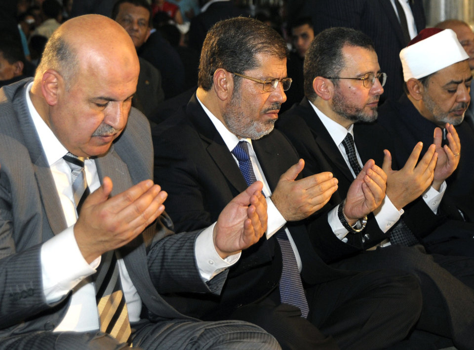Photo - FILE - In this Sunday, Aug. 19, 2012 file photo released by the Egyptian Presidency, Egyptian Vice President, Mahmoud Mekki, left, President Mohammed Morsi, second left, Prime Minister Hesham Kandil, third left, and the Grand Sheik of Al-Azhar, Ahmed el-Tayeb, right, attend Eid el Fitr prayers in Amr Ibn Al-As mosque to mark the start of a three-day Muslim holiday that marks the end of the Muslim holy month of Ramadan. Egypt's state TV says Vice President Mahmoud Mekki has resigned. Mekki's Saturday, Dec. 22, 2012 resignation was announced with more than five hours to go of voting in the second and final phase of a referendum on a disputed, Islamist-backed constitution.  (AP Photo/Egyptian Presidency, File)