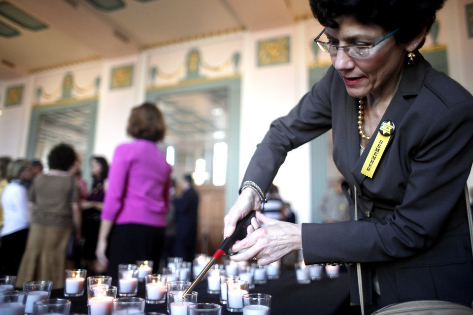 Photo - Cindi Shelby lights a candle in preparation for the 2012 Holocaust Commemoration service Tuesday at the Civic Center Center Music Hall in Oklahoma City.  SARAH PHIPPS - SARAH PHIPPS