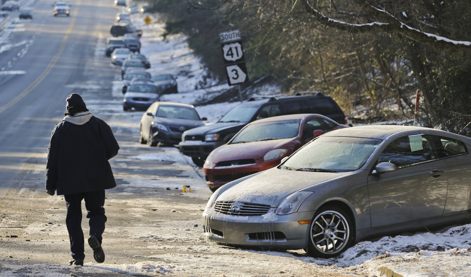 Photo - FILE - In this Thursday, Jan. 30, 2014, file photo, cars abandoned during an earlier snowstorm sit idle along Northside Parkway in Atlanta. With memories of thousands of vehicles gridlocked for hours on icy metro Atlanta highways fresh in their minds, emergency officials and elected leaders in north Georgia were preparing Monday, Feb. 10, 2014, for another round of winter weather. (AP Photo/Atlanta Journal & Constitution, John Spink, File)