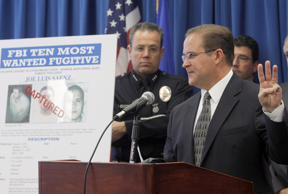Photo -   Bill Lewis, the FBI Los Angeles Assistant Director in Charge, right, and Los Angeles Police Assistant Chief Michael Moore, left, announce the arrest of suspect Joe Luis Saenz, one of the FBI Ten Most Wanted fugitives after he was arrested Thursday, Nov. 22, 2012, in a joint operation with the Mexican government, during a news conference in Los Angeles Monday Nov. 26 , 2012. (AP Photo/Nick Ut)