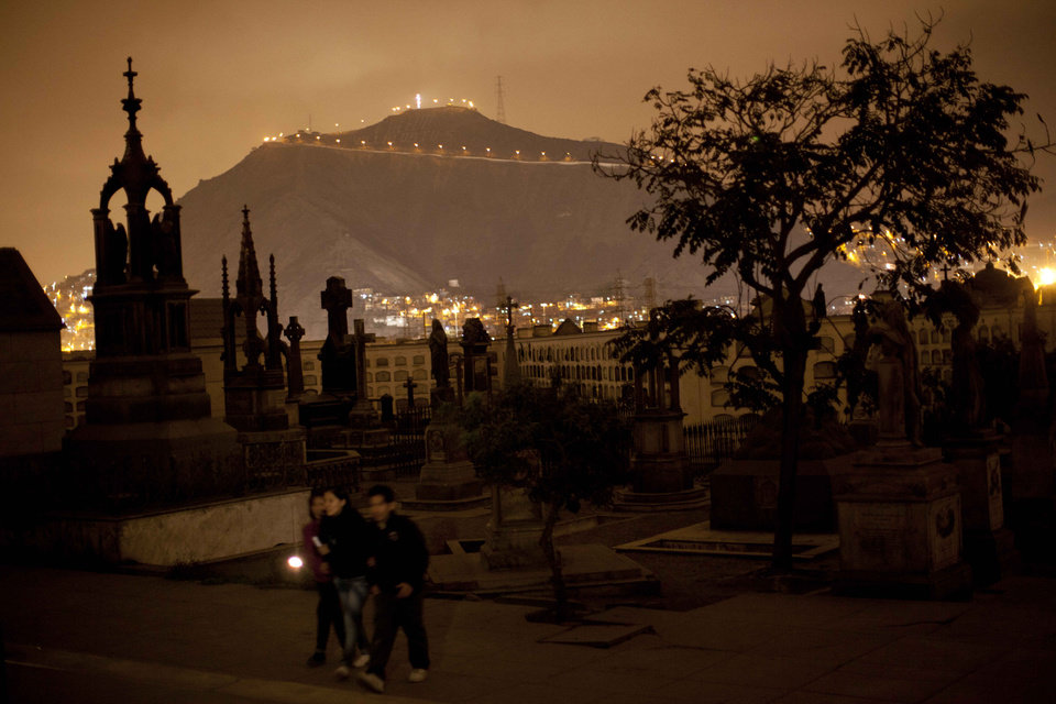 In this Dec. 6, 2012 photo, people use a flashlight as they take a nighttime guided tour through the Presbitero Matias Maestro cemetery in Lima, Peru. There are tombs of popular saints the Vatican doesn\'t recognize. The most popular is Ricardo Espiell, a child who died 119 years ago at age six after supposedly performing miracles. (AP Photo/Rodrigo Abd)