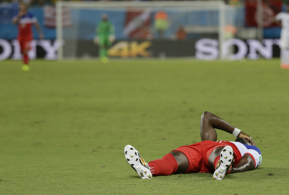 Photo - United States' Jozy Altidore holds his hand to his face as he lies on the pitch after pulling up injured during the group G World Cup soccer match between Ghana and the United States at the Arena das Dunas in Natal, Brazil, Monday, June 16, 2014. (AP Photo/Ricardo Mazalan)