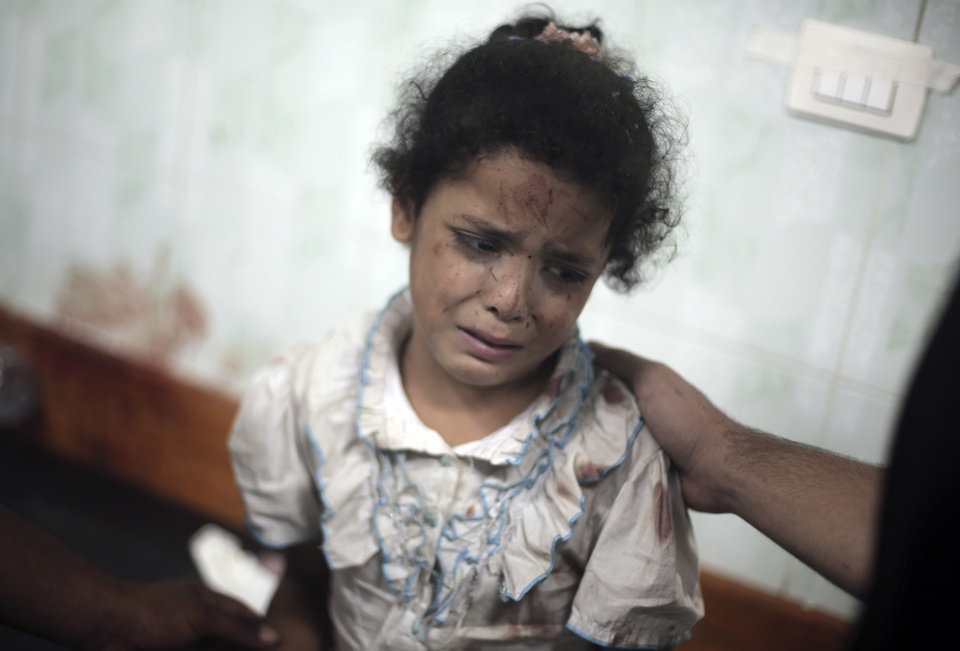 Photo - A Palestinian girl cries while receiving treatment for her injuries caused by an Israeli strike at a U.N. school in Jebaliya refugee camp,  at the Kamal Adwan hospital in Beit Lahiya, northern Gaza Strip, Wednesday, July 30, 2014. Several Israeli tank shells slammed into the crowded U.N. school used as shelter for refugees in the Gaza war early on Wednesday, a Palestinian health official and a U.N. official said. (AP Photo/Khalil Hamra)