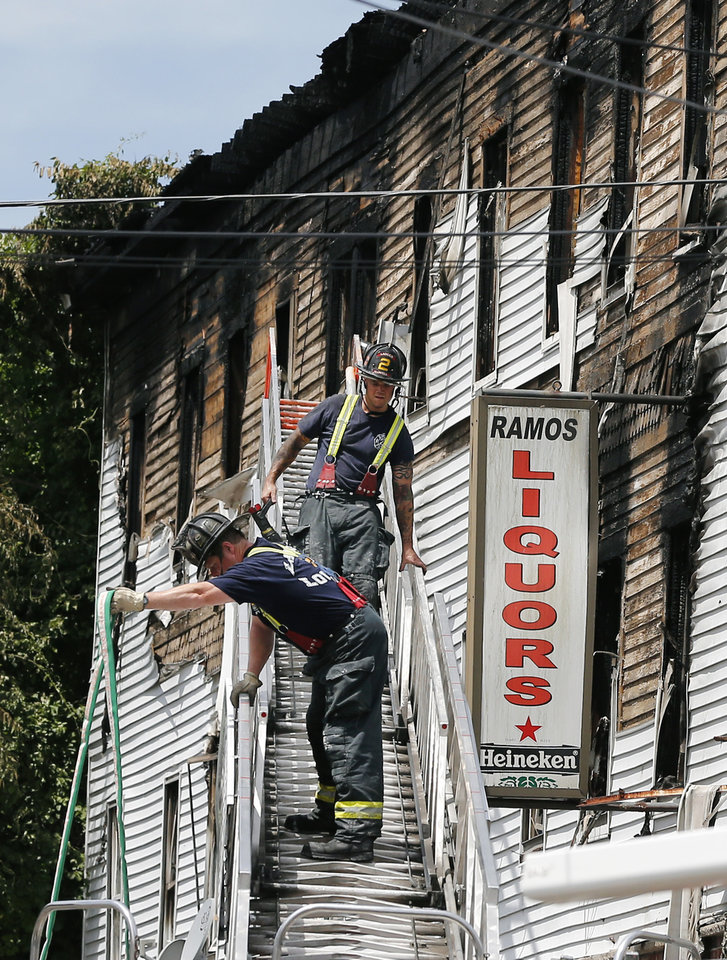 Photo - Firefighters work on a ladder outside a burned three-story apartment and business building in Lowell, Mass., Thursday, July 10, 2014, where officials said four adults and three children died in a fast-moving pre-dawn fire. (AP Photo/Elise Amendola)