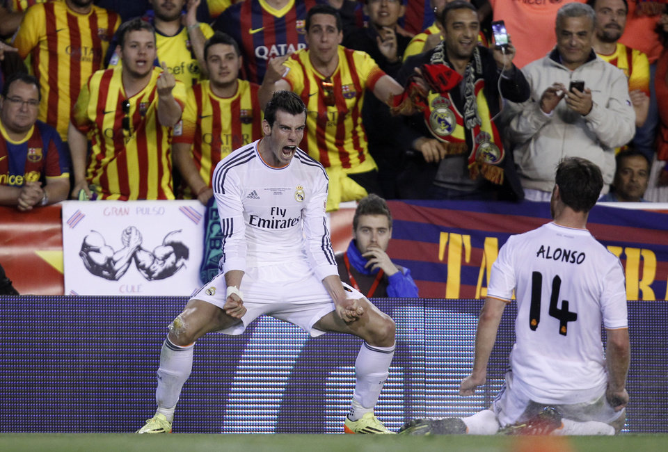 Photo - Real's Gareth Bale, left celebrates scoring his team's 2nd goal during the final of the Copa del Rey between FC Barcelona and Real Madrid at the Mestalla stadium in Valencia, Spain, Wednesday, April 16, 2014. (AP Photo/Alberto Saiz)