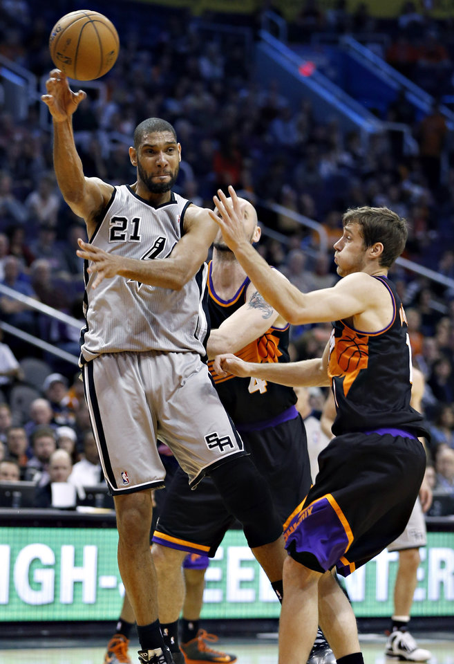San Antonio Spurs' Tim Duncan (21) passes under pressure from Phoenix Suns' Goran Dragic, of Slovenia, during the first half of an NBA basketball game, Sunday, Feb. 24, 2013, in Phoenix. (AP Photo/Matt York)