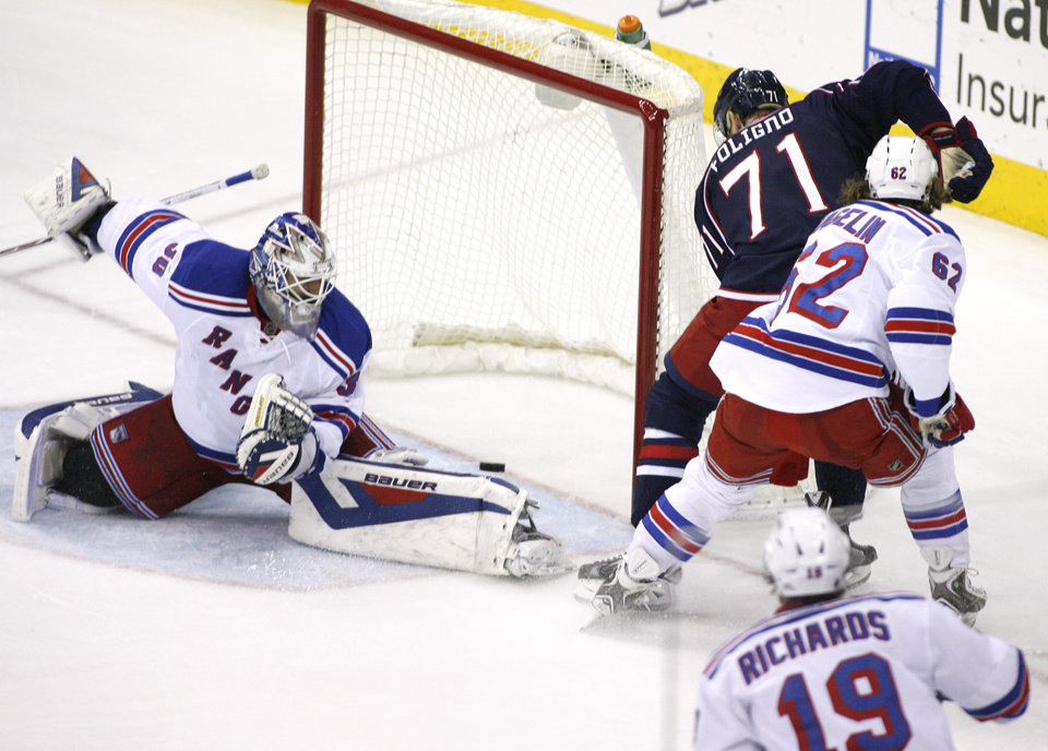 Photo - Columbus Blue Jackets' Nick Foligno (71) shoots off the post past New York Rangers goalie Henrik Lundqvist (30) during the third period of an NHL hockey game, Friday, March 21, 2014, in Columbus, Ohio. (AP Photo/Mike Munden)