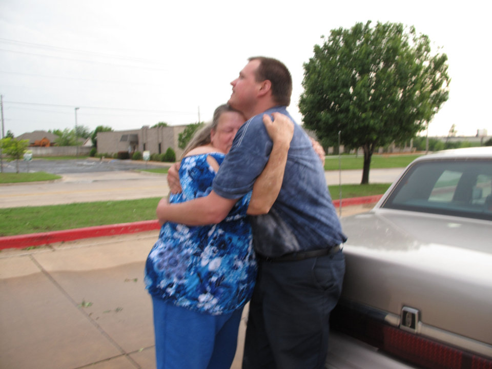Photo - Cecilia Lambert hugs her son Joseph as the two reunite Monday evening in the parking lot of First Baptist Church of Moore after a tornado cut a deadly path through the city of Moore. Photo by Carla Hinton  Carla Hinton - The Oklahoman
