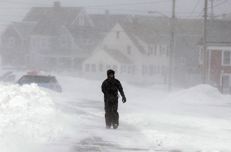 Photo - A passer-by walks through snow and strong wind along an empty street in Marshfield, Mass., Wednesday, Jan. 22, 2014. Temperatures across the state were in the single digits early Wednesday. (AP Photo/Steven Senne)