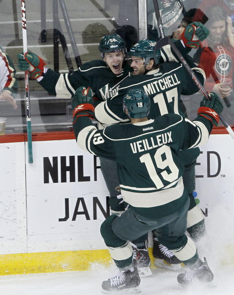 Minnesota Wild left wing Erik Haula, of Finland, celebrates his goal off Dallas Stars goalie Kari Lehtonen with teammates Torrey Mitchell (17) and Stephane Veilleux (19) during the first period of an NHL hockey game in St. Paul, Minn., Saturday, Jan. 18, 2014. (AP Photo/Ann Heisenfelt)