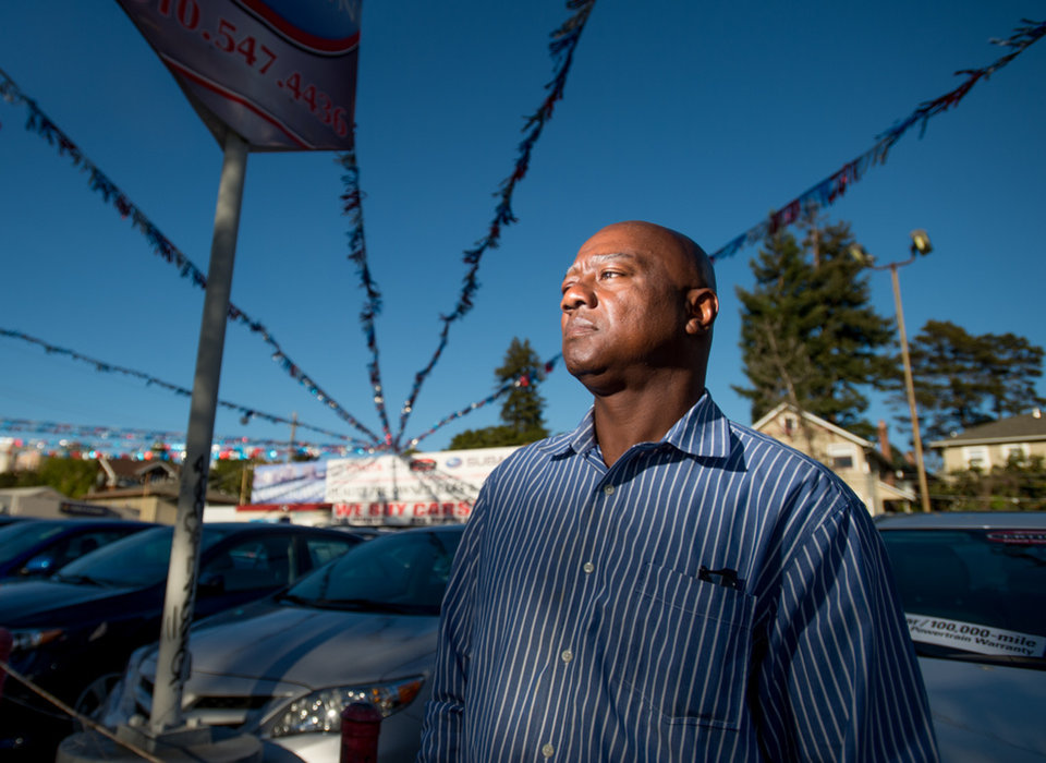 Photo - Arthur Scott, who was paroled in March 2014 after serving time on his 22nd auto theft conviction, stands in front of an Oakland, Calif., Toyota dealership on Tuesday, June 24, 2014. Scott, determined to stay out of jail and currently working while taking vocational classes, says he had stolen more than five cars from the dealership. For him, stable housing was critical, he said. Each time he was released, he found himself homeless or in a halfway house with other men who did drugs and he would get re-arrested within days. (AP Photo/Noah Berger)