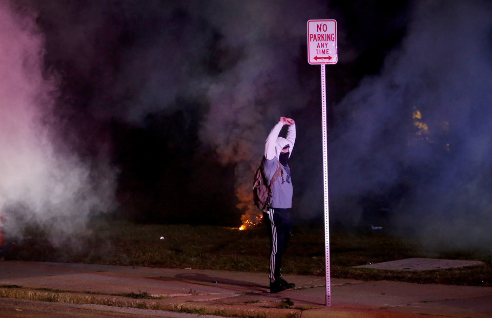 Photo - A protester holds their hands in the air tear gas goes in the air in  front of the Oklahoma City Police Department in Oklahoma City, Sunday, May 31, 2020. The protest was in response to the death of George Floyd. [Sarah Phipps/The Oklahoman]