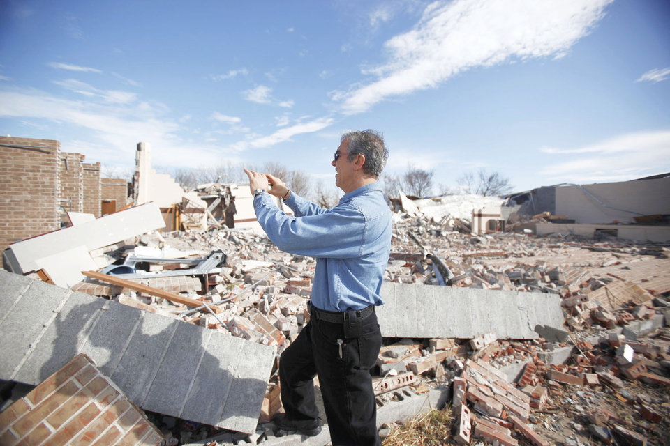 Allen Zahrai with the National Severe Storms Laboratory walks past debris at the Ardmore Adventist Academy near the Majestic Hills neighborhood north of Ardmore on Thursday. PHOTO BY SARAH PHIPPS, THE OKLAHOMAN