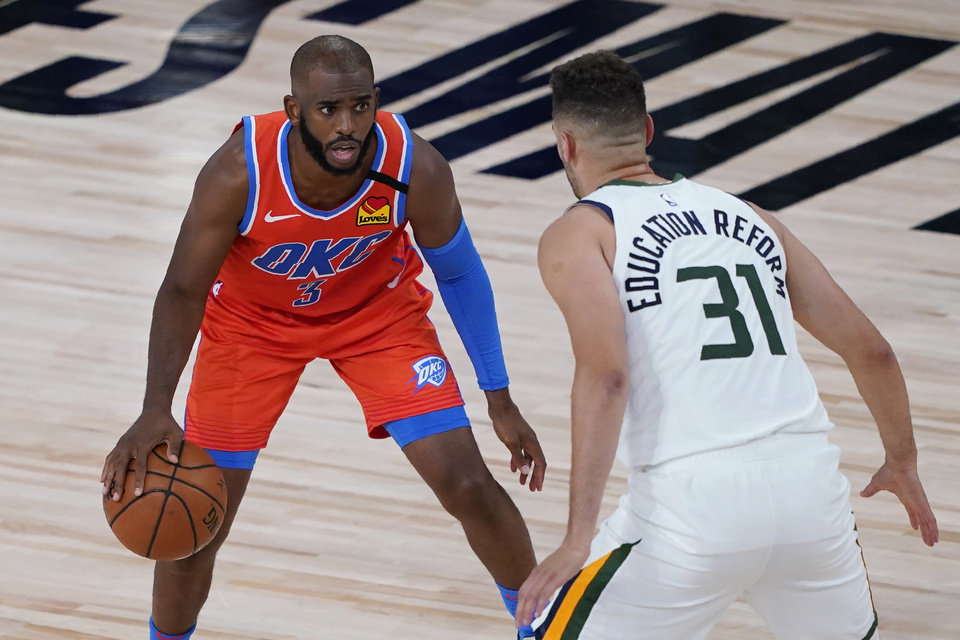 Photo - Utah Jazz's Georges Niang (31) guards Oklahoma City Thunder's Chris Paul (3) during the first half of an NBA basketball game Saturday, Aug. 1, 2020, in Lake Buena Vista, Fla. (AP Photo/Ashley Landis, Pool)