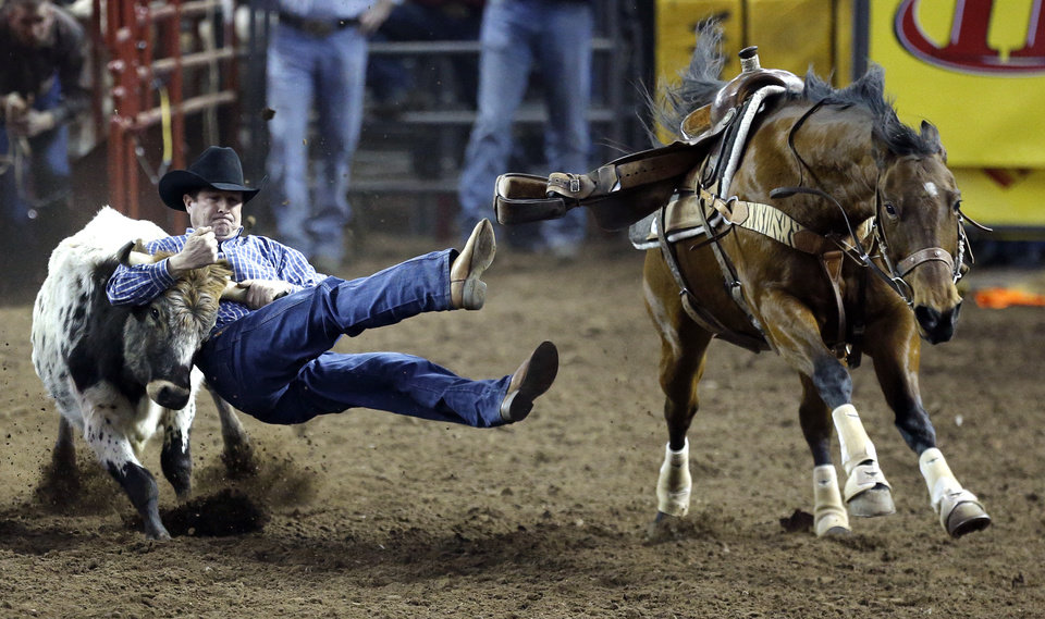 Photo - Walt Sherry of Atwood, Okla., wrestles a steer after jumping off Stevie during the International Finals Rodeo at the State Fair Arena in Oklahoma City, Friday, Jan. 17, 2014.  Photo by Sarah Phipps, The Oklahoman
