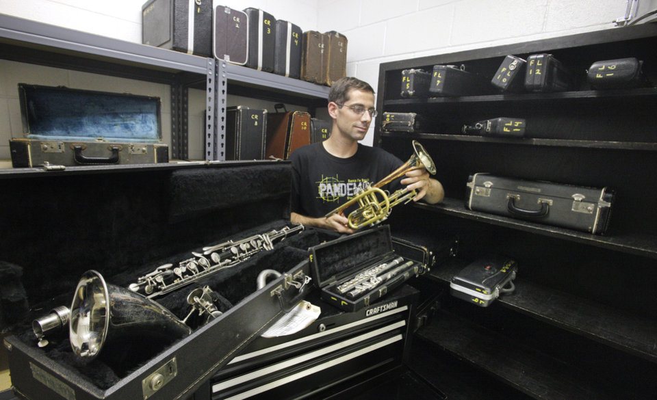 Scott Filleman, band director, holding a cornet, with a bass clarinet and flute in front, all in need of repair work that are used in the band program at Santa Fe South Middle School in Oklahoma City Friday, July 20, 2012. Photo by Paul B. Southerland, The Oklahoman