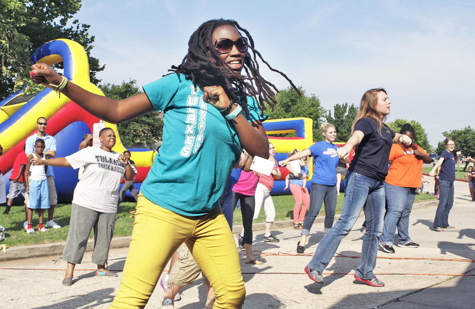 Tulakes Elementary School Social Worker Jamese Siranga and other teachers and staff do a dance for students at the school in Oklahoma City, OK, during a back-to-school bash, Saturday, August 17, 2013,  Photo by Paul Hellstern, The Oklahoman <strong>PAUL HELLSTERN - Oklahoman</strong>