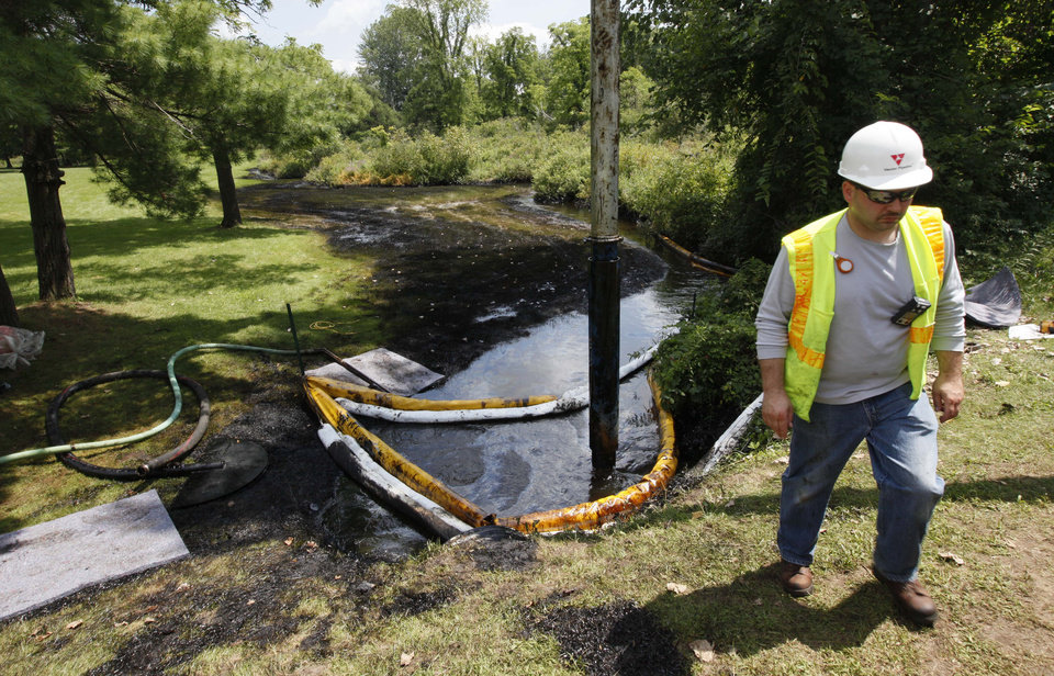 Photo -   FILE - In this July 29, 2012 file photo, a worker monitors the water in Talmadge Creek in Marshall Township, Mich., near the Kalamazoo River as oil from a ruptured pipeline, owned by Enbridge Inc, is vacuumed out the water. Federal investigators are expected to present their findings Tuesday, July 10, 2012 on the likely cause of a pipeline rupture that spilled more than 800,000 gallons of crude oil into the river nearly two years ago. (AP Photo/Paul Sancya, File)
