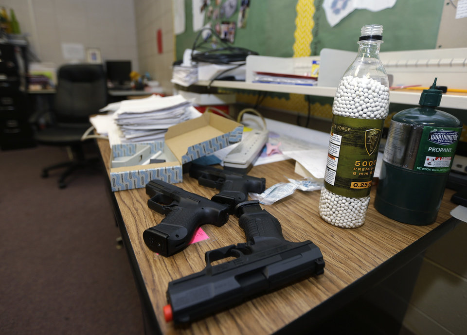 In this photo taken July 11, 2013, practice air-powered handguns sit on a teacher\'s desk in a classroom at Clarksville High School in Clarksville, Ark. Twenty Clarksville School District staff members are training during the summer to be armed security guards on campus. (AP Photo/Danny Johnston)