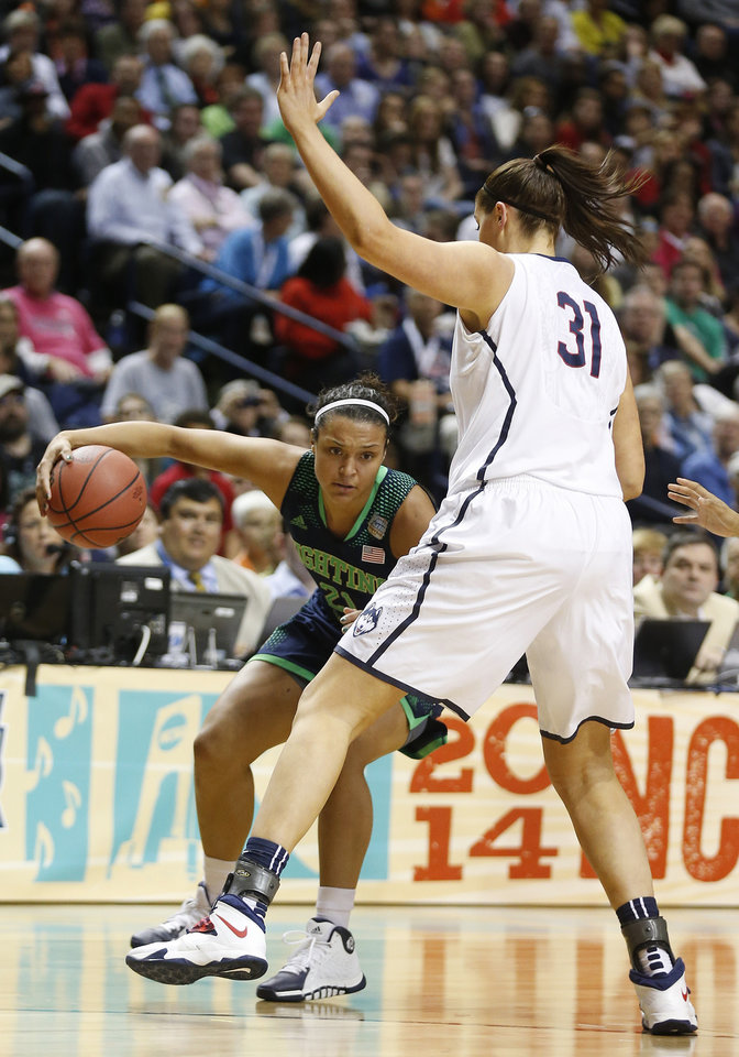 Photo - Notre Dame guard Kayla McBride (21) moves by Connecticut center Stefanie Dolson (31) during the first half of the championship game in the Final Four of the NCAA women's college basketball tournament, Tuesday, April 8, 2014, in Nashville, Tenn. (AP Photo/John Bazemore)