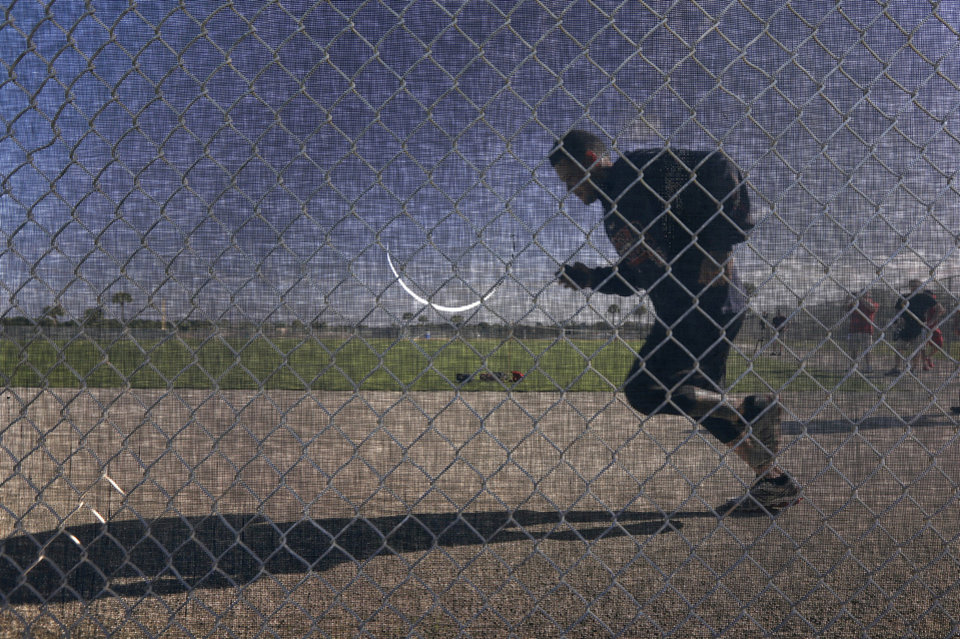 Photo - St. Louis Cardinals catcher Yadier Molina jogs along a fence during an informal spring training baseball practice Wednesday, Feb. 12, 2014, in Jupiter, Fla. Cardinals pitchers and catchers first official practice is scheduled for Thursday. (AP Photo/Jeff Roberson)
