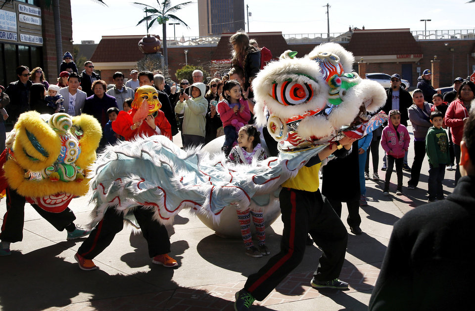Photo -  Members of the youth group from the Vien Minh Buddhist Center in Moore don colorful costumes to dance a lively lion dance during the Oklahoma City Asian District's Chinese New Year festival on Feb. 21, 2015. The event was in the parking lot of Super Cao Nguyen supermarket near NW 26 and N Military Avenue. The Asian District was born with the arrival of Vietnamese War refugees after the fall of Saigon in 1975, and eventually will be considered historic. [PHOTO BY JIM BECKEL, THE OKLAHOMAN ARCHIVES]