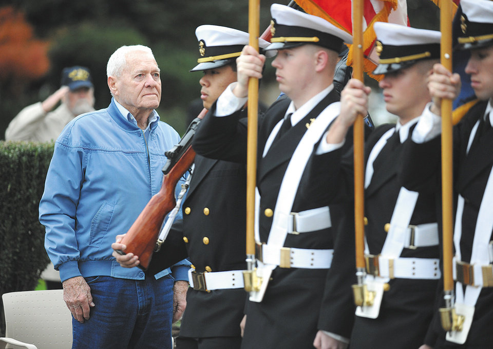 USS Oklahoma survivor David Russell, 92, of Albany, Ore.  stands at attention as the Oregon State University Naval ROTC Color Guard retires the colors at a Pearl Harbor remembrance ceremony on the steps of the Linn County Courthouse, Friday Dec. 7, 2012 in Albany.  (AP Photo/Albany Democrat-Herald, Mark Ylen)