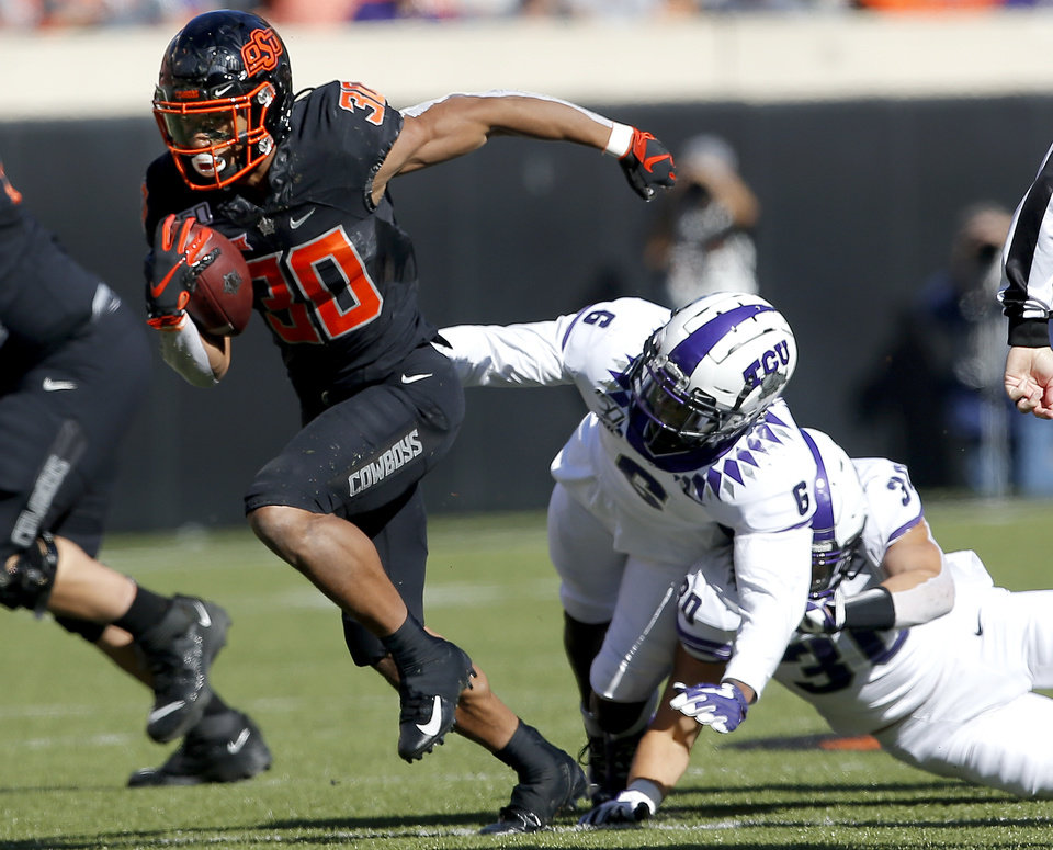Photo - Oklahoma State's Chuba Hubbard (30) tries to get by TCU's Innis Gaines (6) in the first quarter during the college football game between the Oklahoma State University Cowboys and the TCU Horned Frogs at Boone Pickens Stadium in Stillwater, Okla.,  Saturday, Nov. 2, 2019. [Sarah Phipps/The Oklahoman]