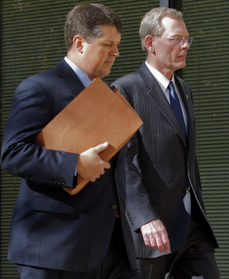David Rainey, right, a former vice president of exploration for BP America, enters Federal Court before he is arraigned for obstructing a Congressional investigation in New Orleans, Wednesday, Nov. 28, 2012. (AP Photo/Matthew Hinton)