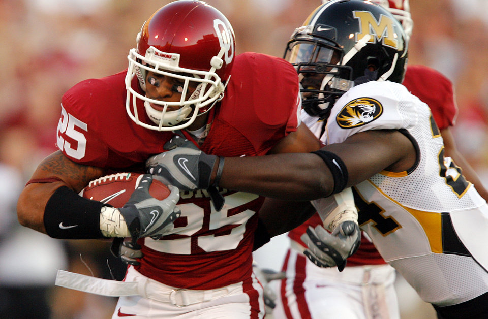 Photo - Oklahoma's D.J. Wolfe (25) gets past Missouir's Derrick Washington (24) as he returns an interception during the first half of the college football game between  the University of Oklahoma Sooners (OU) and the University of Missouri Tigers (MU) at the Gaylord Family Oklahoma Memorial Stadium on Saturday, Oct. 13, 2007, in Norman, Okla.By CHRIS LANDSBERGER, The Oklahoman