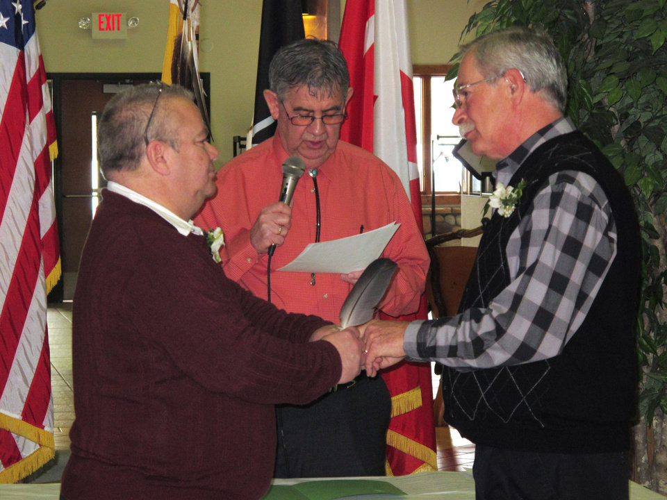 Photo - Tim LaCroix, left, and Gene Barfield recite their nuptial vows in the governmental building of the Little Traverse Bay Bands of Odawa Indians, Friday, March 15, 2013, in Harbor Springs, Mich. Tribal Chairman Dexter McNamara, center, officiated during the wedding after signing a measure approved by the tribal council that allows same-sex marriages on the reservation. (AP Photo/John Flesher)